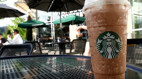 Coquitlam, BC, Canada - May 04, 2016 : One side of people drinking Starbucks coffee on sunny day, focus on ice frappuccino