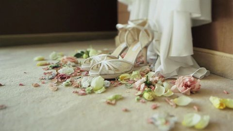 Beautiful luxury pair of high heels white bridal shoes lace sandals standing on carpet with rose flowers petals around waiting for bride on her wedding day. Close-up. Dolly