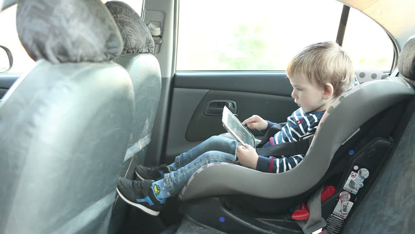 little boy using a tablet sitting in a car seat car hd stock footage clip