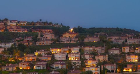 Timelapse of the Full moon rising over many hilltop large Estates homes in Newport Coast / Newport Beach, California.  The warm hue on the homes is a result of the setting sun illuminating the homes.