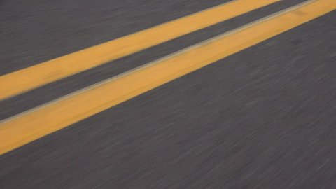 Driving road with swirling double yellow lines that break into four lines. 4K UHD 3840x2160