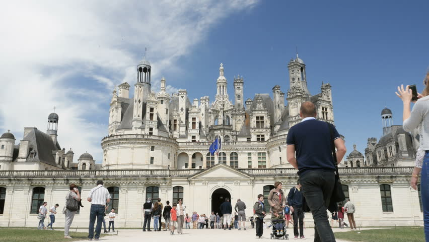 CHAMBORD, LOIR-ET-CHER, FRANCE - CIRCA 2016: Tourists admiring and visiting the famous Chateau de Chambord one summer spring day with warm weather and blue sky
