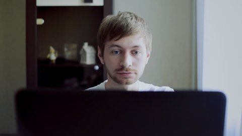 a young guy in front of laptop receiving negative news, upset and surprised