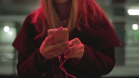 Teenage girl with long blonde hair walking along the street,listening to the music,dancing, smiling, wearing headphones at night under red lights, wearing black coat. Tracking shot.