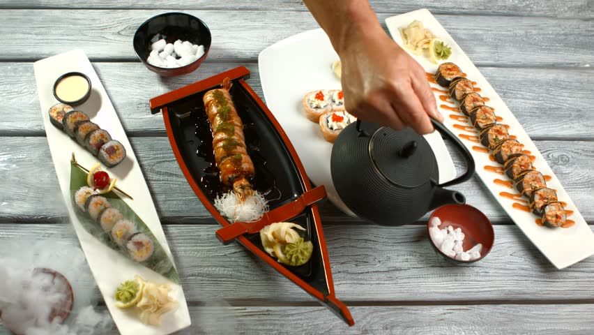 Different plates with sushi rolls. Hand with kettle pouring liquid. Sushi served with dry ice. Artwork created by japanese chef. | Shutterstock HD Video #16810945