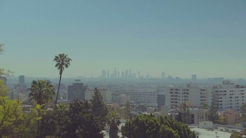 Establishing daytime shot of downtown LA skyline with palm tree in Los Angeles, California. Los Angeles, CA - USA: January, 2016