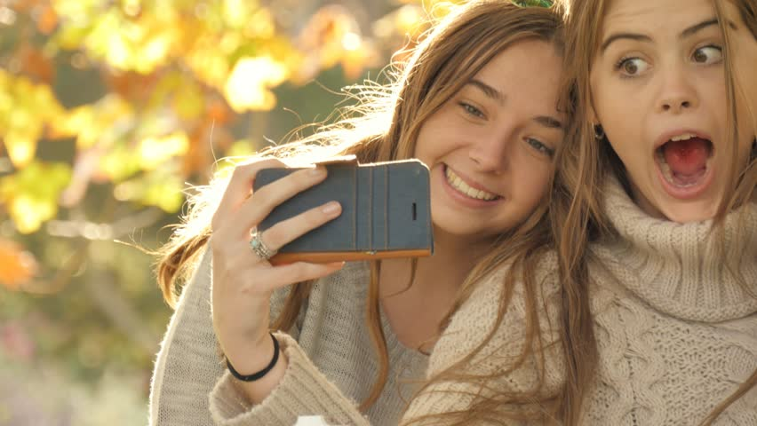 Two best friends with cell phone camera taking photos under autumn fall