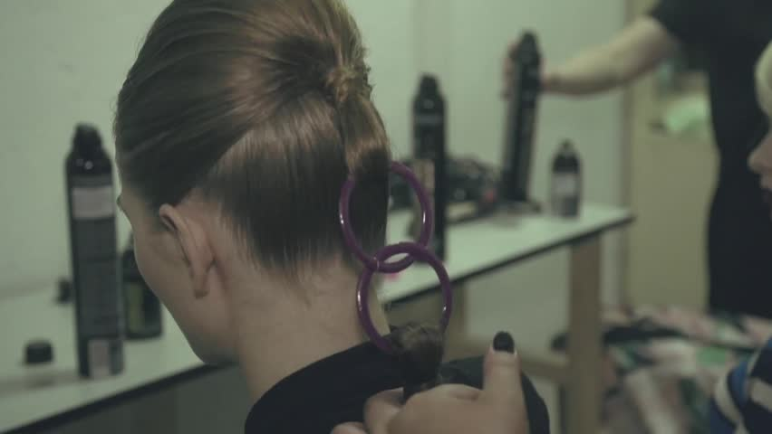 Master making hair style, fashion show backstage. Professional barber working with hair of a woman.