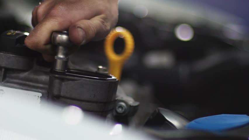 Auto mechanic repair engine at car repair shop. Slow motion