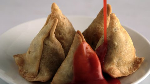 This is a shot of Samosas (samosa) revolving , as ketchup is pouring on. Delicious samosas with Red color tomato sauce pouring. Samosas are distinctly triangular. Shot at high speed on Phantom camera.