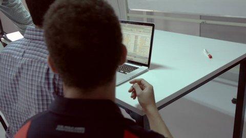 2 Shots: Businessmen around laptop view data on screen. Three men sitting around a laptop analyze data in a spreadsheet.