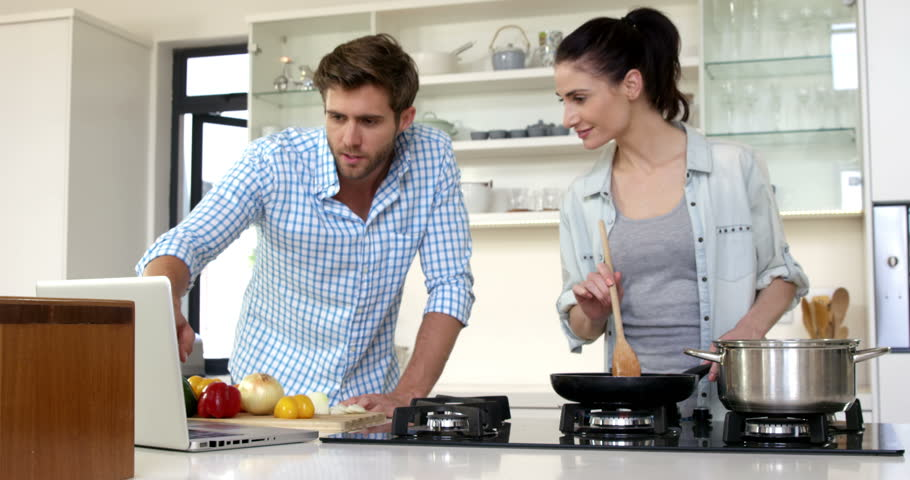 Cute couple learning how to cook by watching a tutorial on internet