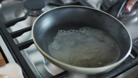 Barcelona, Spain - November 11, 2012: Woman swirling boiling water in pan over stovetop