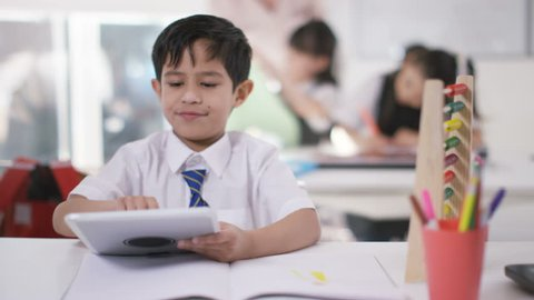 4K Young school children in class with little boy using abacus & computer tablet UK - April, 2016