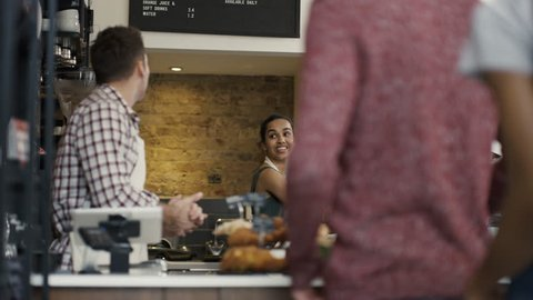 4K Cheerful worker serving a customer who uses smartphone to pay in coffee shop. UK - April, 2016