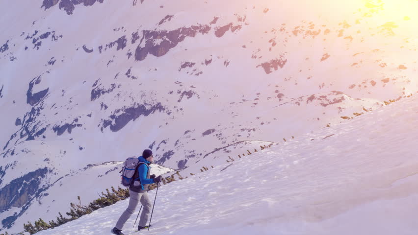 Aerial Drone Flight Over Young Hiker Man Walking up Climbing Mountain Ridge Dangerous Journey Hard Work Agility Fitness Winter Adventure Vacation Concept | Shutterstock HD Video #16998955