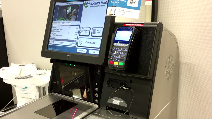 Burnaby, BC, Canada - May 30, 2016 : Close up of man paying foods at self-check out counter inside Price Smart foods store