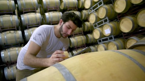 Man smelling wine ntérieur a barrel and noting on a tablet.Wine Barrels in Winery Cellar Bordeaux Wineyard