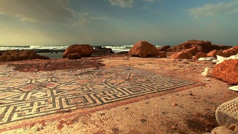Low angled view of the Caesarea Israel ruin, mosaic on the beachfront of the Mediterranean, with waves, sky and clouds in the background.
