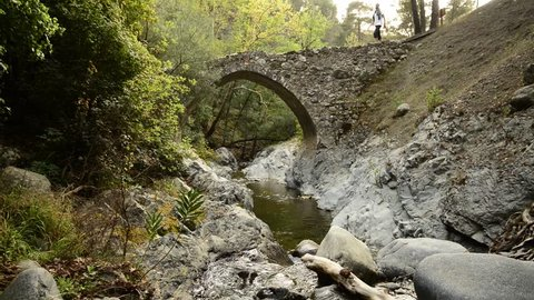 Bearded hiker goes through the medieval Venetian bridge, stops for rest, sits in the edge, enjoying life looking at the setting sun. Wonderful evening in Cyprus.