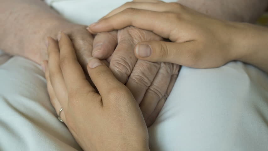 A young female hands comforting an elderly pair of hands of old women close up