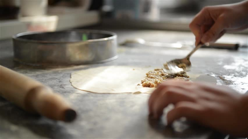 cook prepares meat pies, working with the dough and filling, close-up