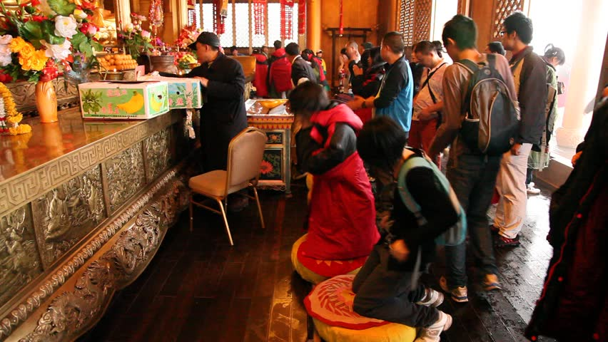 MOUNT EMEI, CHINA - JULY 22, 2009: Buddhists pray inside the Golden Summit Temple on July 22, 2009 on Mount Emei.
