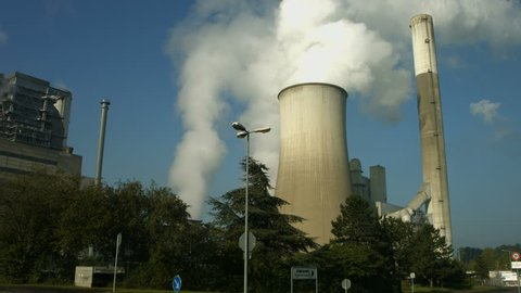 Close up shot of a huge lignite fired power plant with tall and dirty chimneys and steaming cooling towers.