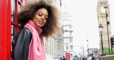 Smiling portrait of young woman close to red telephone box in London. Big Ben in the background.