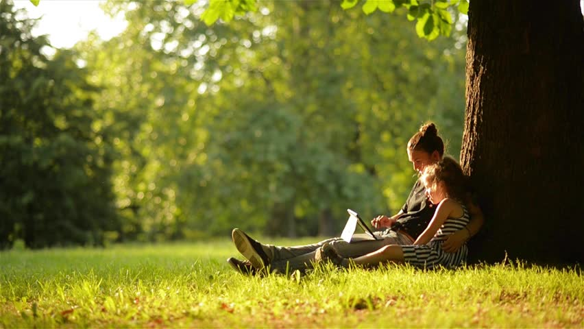 Young mother and her daughter playing on a tablet and a dog in a beautiful park | Shutterstock HD Video #17126203
