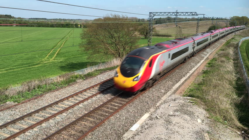 Northamptonshire, UK - May 06, 2016: A Virgin Trains Pendolino tilting electric express passenger train traveling north at speed on the West Coast mainline railway in England. | Shutterstock HD Video #17127745
