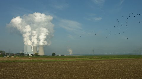 Long shot of agricultural land and fields with a huge lignite fired power plant with steaming cooling towers in the background.