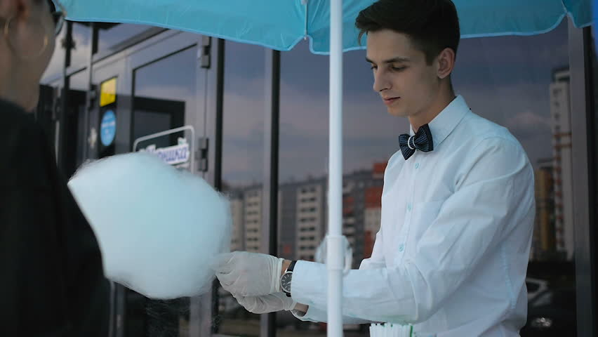 Young guy making cotton candy on a special machine, wears bow tie, behind him balloons | Shutterstock HD Video #17226025
