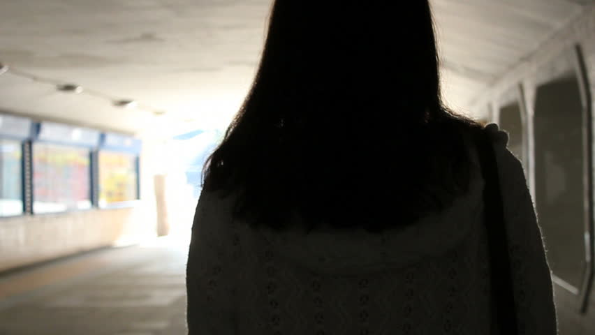 girl walks towards light .slowmotion.