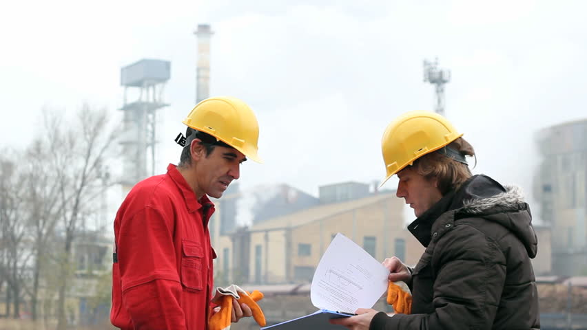 Two Co-Workers Discussing a Document. Supervisor in yellow hardhat , talking to factory worker outside the industrial facility. HD 1080i. Canon EOS 550D.