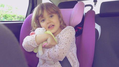 Happy baby girl sitting in car singing hugging plush toy 4K retro style