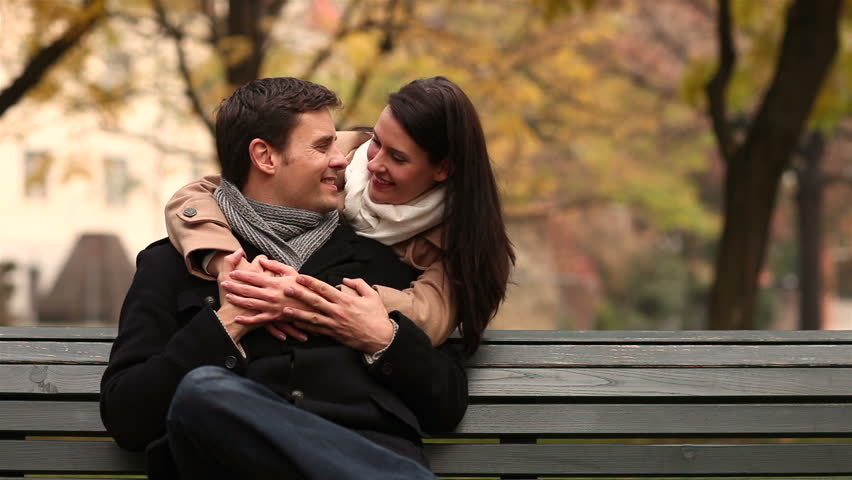 Woman embracing and kissing man in park and both holding thumbs up