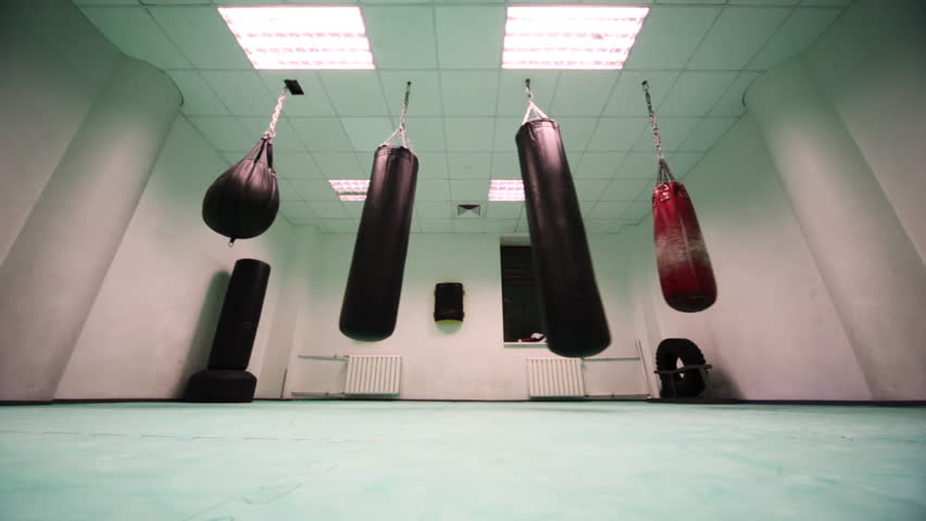 four different size punching bag hang in boxing training room, wide view