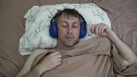 Male night shift worker sleeping in a bed during the day while wearing noise blocking earmuffs to get a good relaxing rest.
