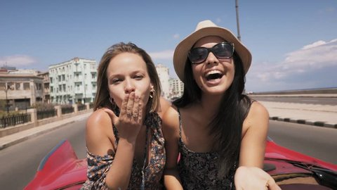 Female friends on holidays, people traveling, young women having fun on vacation, two happy girls smiling in Havana, Cuba, laughing on old classic convertible car, blowing kiss. Slow motion