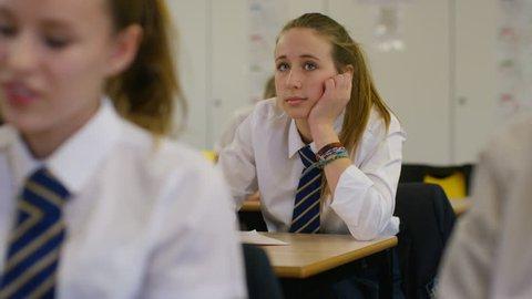 4K Bored girl sitting at desk in school classroom. Shot on RED Epic. UK - April, 2016