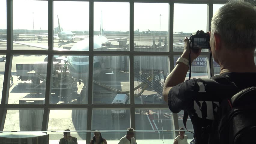, Thailand-09 April, 2016: 4k, Asian Photographer takes pictures with DSLR camera of the plane in the Suvarnabhumi airport at Thailand. Travellers walking inside airport terminal in Bangkok-Dan | Shutterstock HD Video #17328925