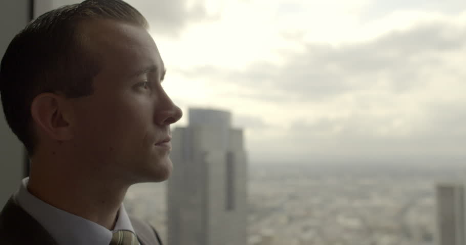 Handsome young business man looks across Los Angeles from Downtown office window.  Big close up with sunrise sky, dolly shot originally recorded in 4K | Shutterstock HD Video #17338228
