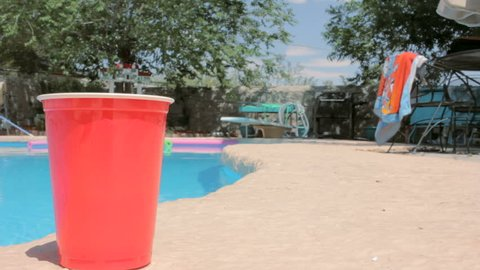 A red solo cup sits on the side of a swimming pool during spring break. A beach towel flaps in the background with a pina colada sitting by the water. The shot embodies relaxation and paradise.