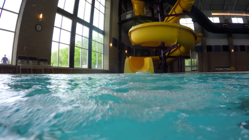 A father takes his little boy down a fun yellow waterslide at the indoor pool | Shutterstock HD Video #17353765