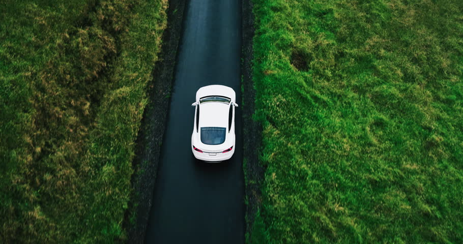 Aerial view electric car driving on country road, luxury car driving through mist at dusk with headlights | Shutterstock Video #17354431