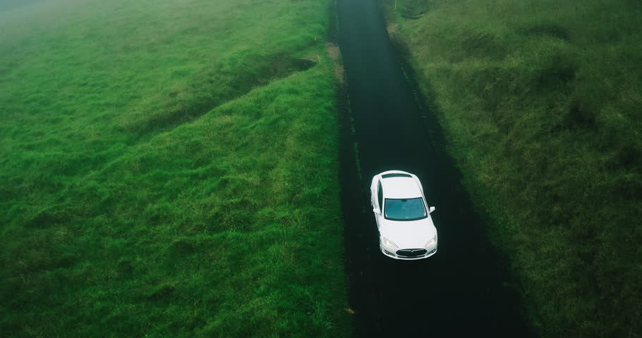 Aerial view electric car driving on country road, luxury car driving through mist at dusk with headlights | Shutterstock HD Video #17354464