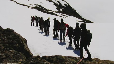 Group of alpinists walk up to snow mountain. Team. Dangerous hobby. Sunny day. Equipment. Rope