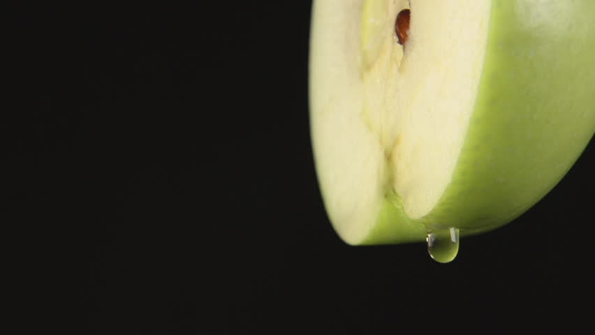 SLOW MOTION: A drops of a juice drip from a green apple