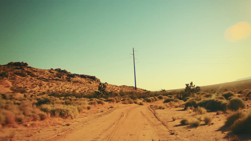 Driving on a Dirt Road in the Hot Desert